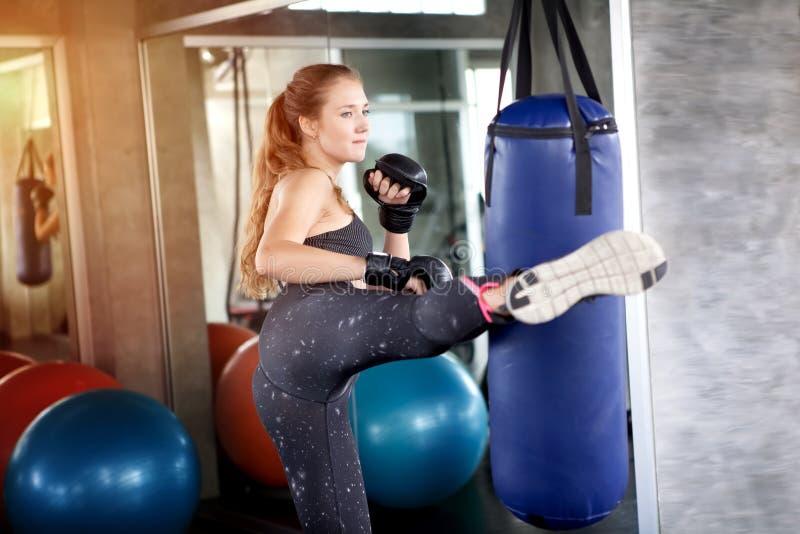 ung konditionflicka som gör övningen som sparkar stansa påsen på idrottshallen wo royaltyfria bilder