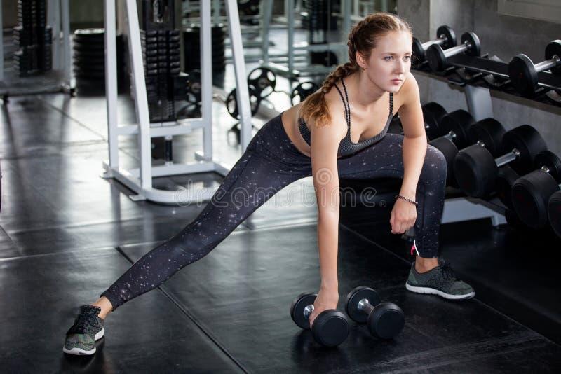 ung konditionflicka som g?r ?vningen som ?r satt med hanteln i idrottshall kvinna, i sportsweargenomköraresträckning arkivfoto