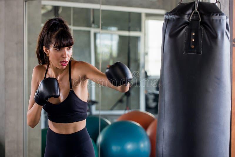 ung konditionflicka som g?r ?vningen som sl?r stansa p?sen p? en boxningstudioidrottshall kvinnaboxare i sportswear som utarbetar arkivbild