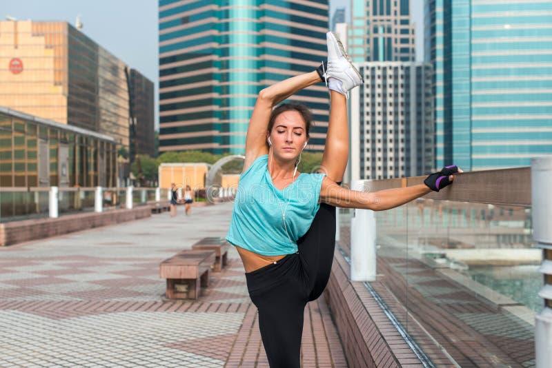 Ung konditionkvinna som gör stående kluven övning på stadsgatan Sportig passformflicka som utarbetar sträckning utomhus arkivfoton