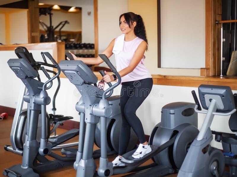 Ung konditionkvinna som utarbetar i idrottshallen Kvinna som utarbetar på motionscykelen arkivbilder