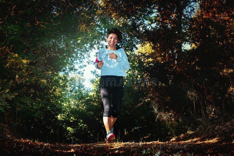 Ung konditionkvinnaspring på skogslingan fotografering för bildbyråer