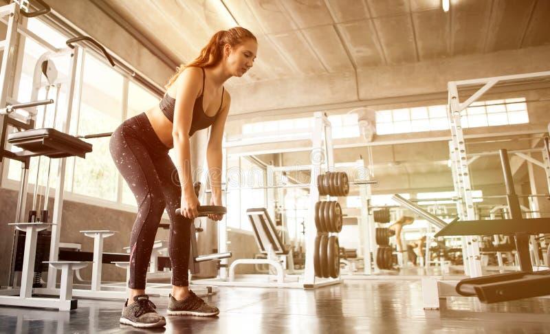 ung konditionsportflicka som gör övningen som är satt med viktskivstångplattan i idrottshall kvinnan i sportsweargenomkörare förs royaltyfri foto