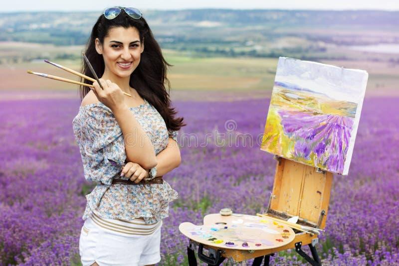 Ung konstnärmålning i lavendelfält royaltyfria foton
