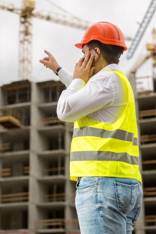 Ung konstruktionstekniker i hardhat som talar vid telefonen och pekar på byggnad under konstruktion royaltyfria bilder