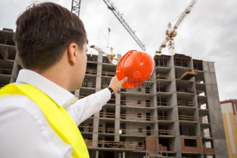 Ung konstruktionstekniker som pekar på byggnad under tankeskapelse arkivbild