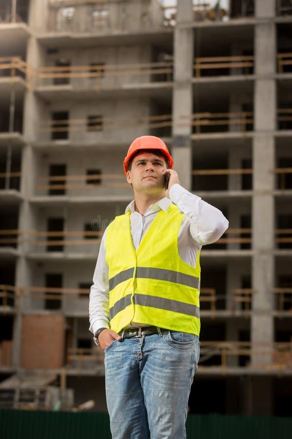 Ung konstruktionstekniker som talar vid telefonen på byggnadsplats royaltyfria bilder
