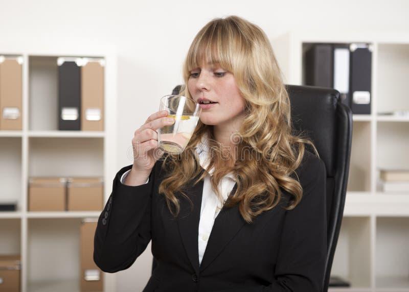Ung kontorsarbetare som tycker om ett exponeringsglas av vatten royaltyfria foton