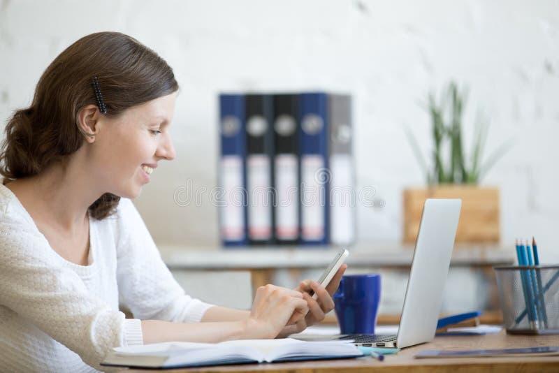 Ung kontorskvinna som ser smartphoneskärmen fotografering för bildbyråer