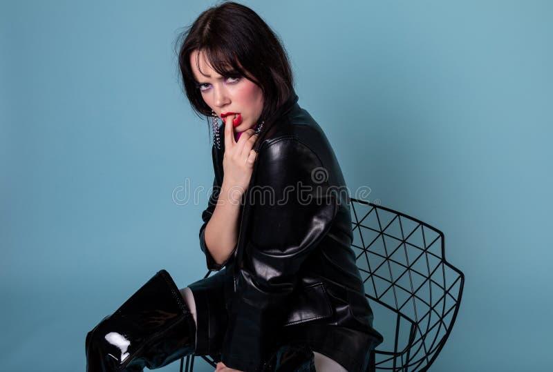 Ung kort modell för svart hår i det svarta läderomslaget som sitter på stol royaltyfri foto