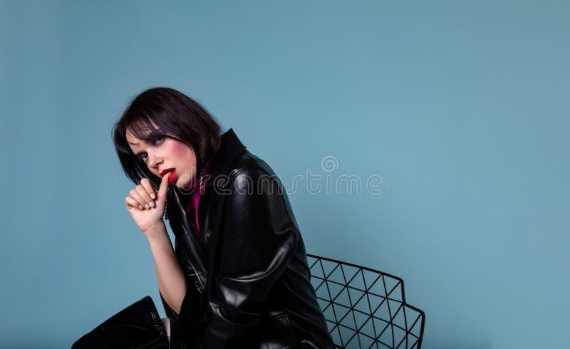 Ung kort modell för svart hår i det svarta läderomslaget som sitter på stol arkivfoto