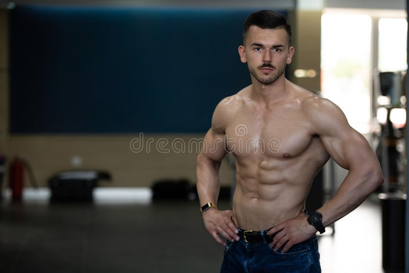 Ung kroppsbyggare i jeans som b?jer muskler arkivfoto