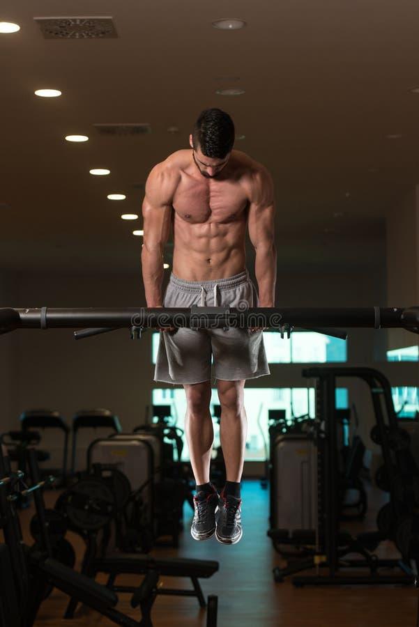 Ung kroppsbyggare som övar triceps som gör dopp på stång royaltyfria bilder