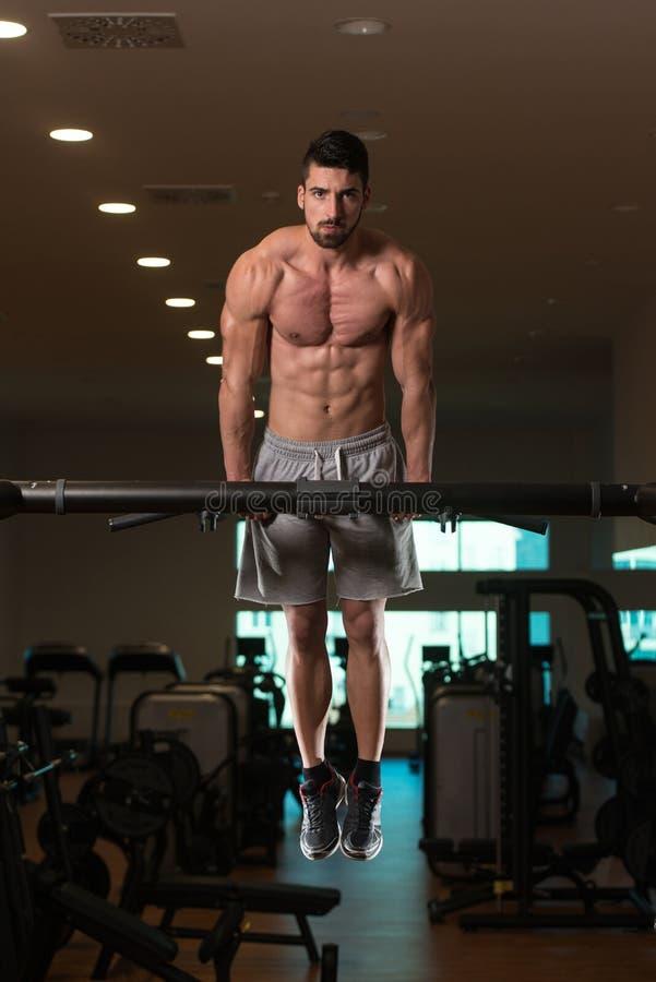 Ung kroppsbyggare som övar triceps som gör dopp på stång arkivbilder