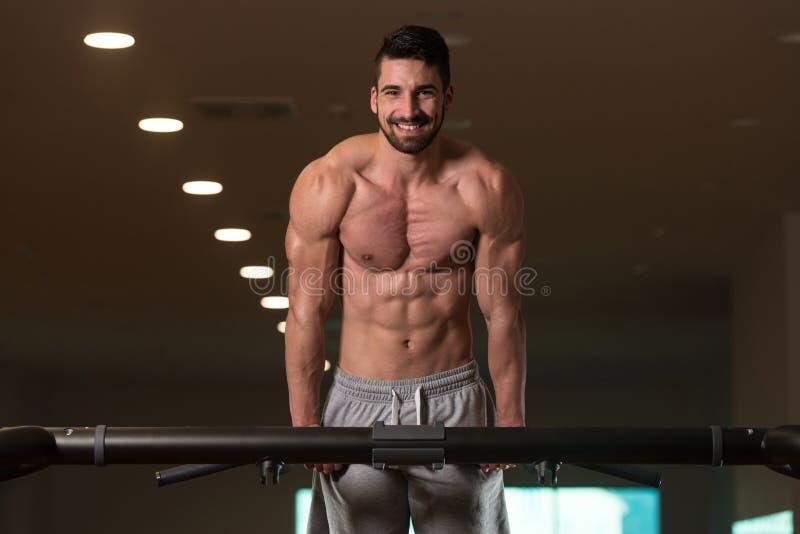 Ung kroppsbyggare som övar triceps som gör dopp på stång royaltyfria foton