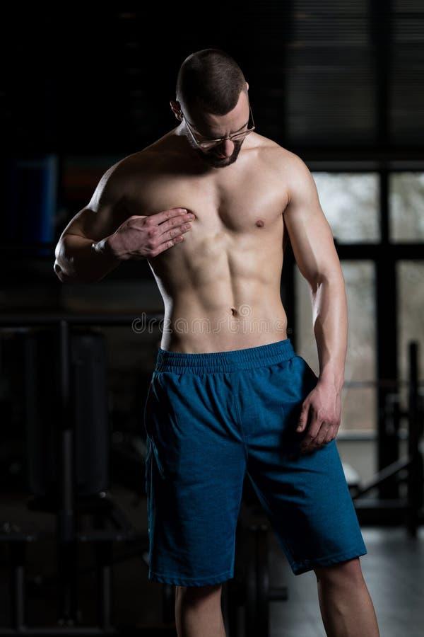 Ung kroppsbyggare som böjer muskler royaltyfri foto