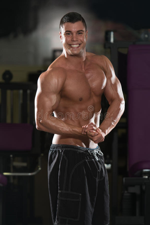 Ung kroppsbyggare som böjer muskler royaltyfri bild