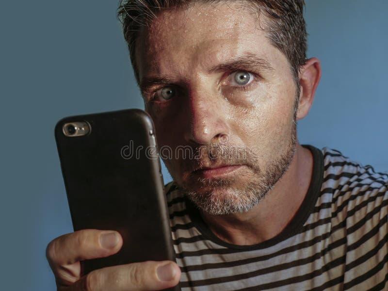 Ung kuslig och galen mobiltelefonknarkareman som tvångsmässigt använder cellen med kusligt och onormalt framsidauttryck i interne royaltyfri foto