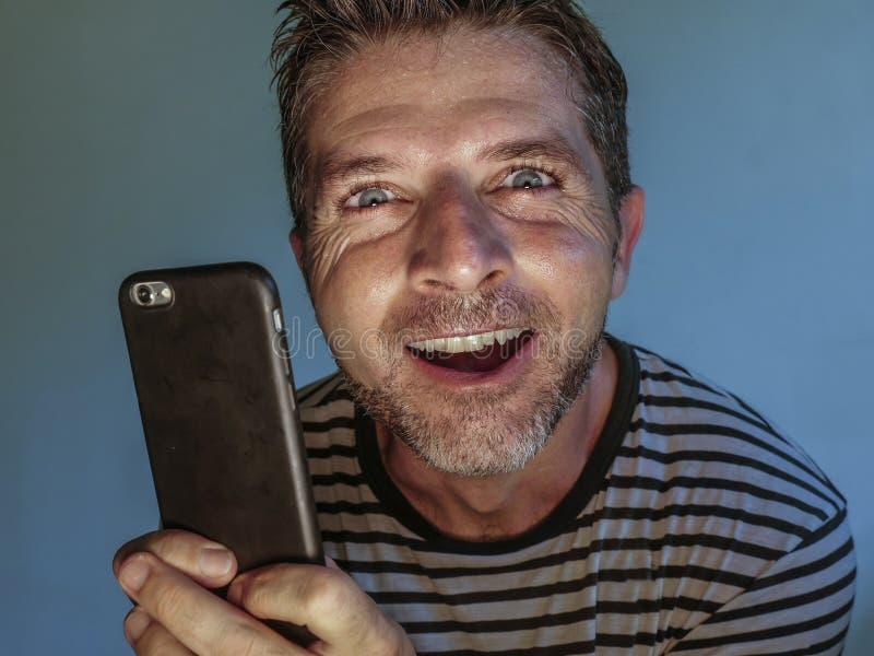 Ung kuslig och galen mobiltelefonknarkareman som tvångsmässigt använder cellen med kusligt och onormalt framsidauttryck i interne royaltyfri bild