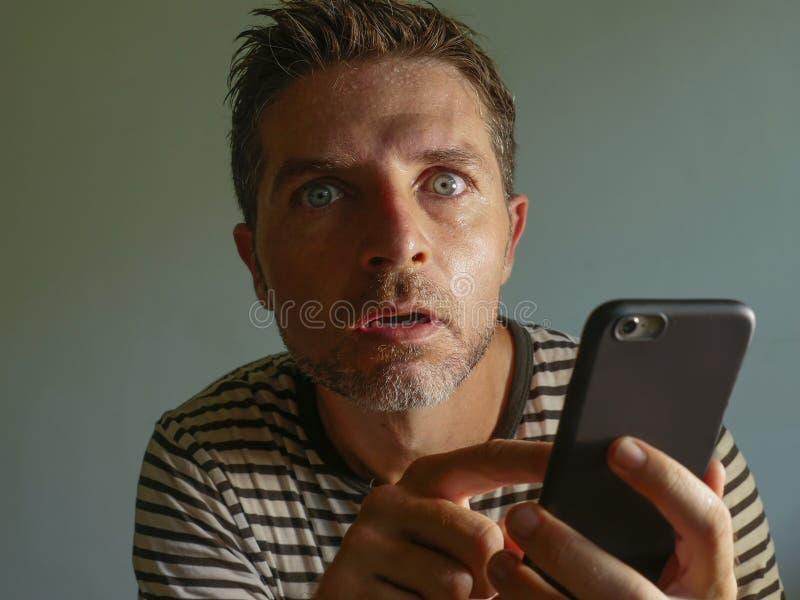 Ung kuslig och galen mobiltelefonknarkareman som tvångsmässigt använder cellen med kusligt och onormalt framsidauttryck i interne royaltyfria foton