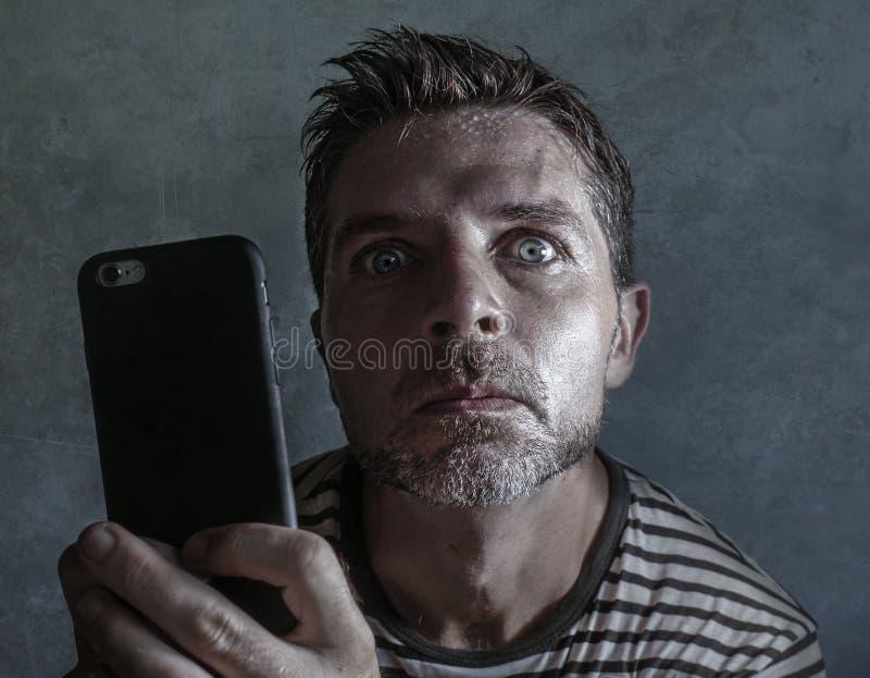 Ung kuslig och galen mobiltelefonknarkareman som tvångsmässigt använder cellen med kusligt och onormalt framsidauttryck i interne arkivfoton