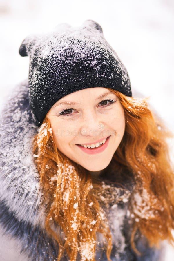 Ung kvinna över snöig wood bakgrund för vinter royaltyfria bilder