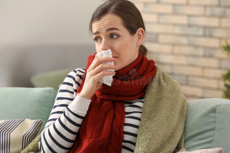 Ung kvinna dåligt med influensa hemma arkivbild