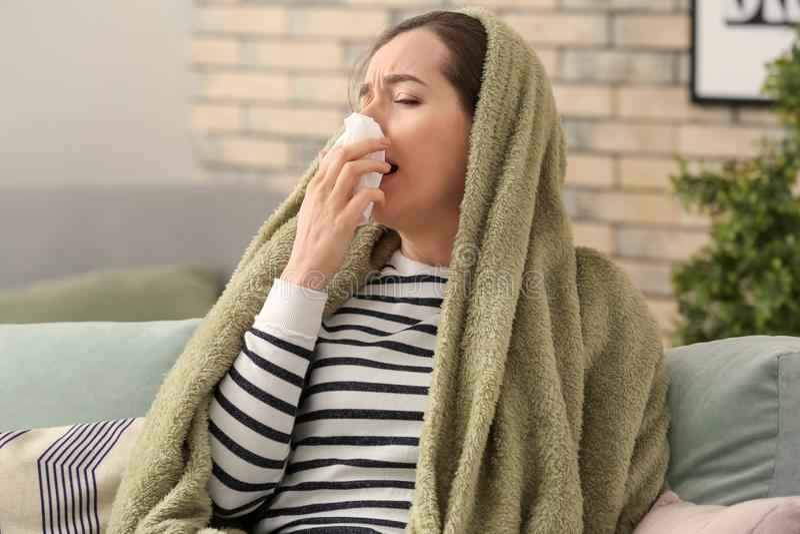 Ung kvinna dåligt med influensa hemma arkivfoton