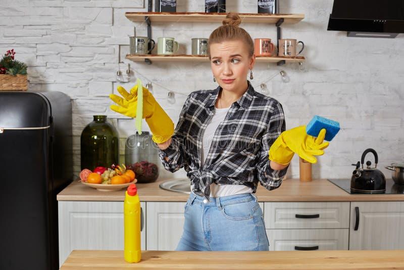 Ung kvinna eller hemmafru i gummihandskar som torkar tabellen med hemmastatt kök för microfibertorkduk royaltyfri foto
