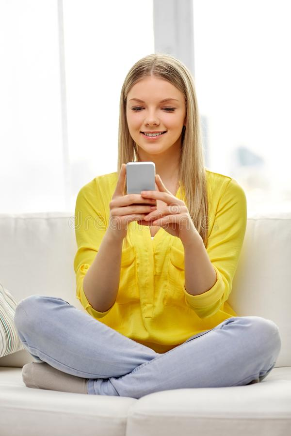 Ung kvinna eller tonårig flicka med smartphonen hemma arkivbilder