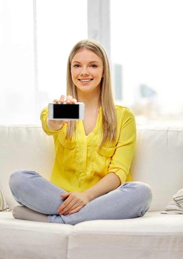 Ung kvinna eller tonårig flicka med smartphonen hemma arkivfoto