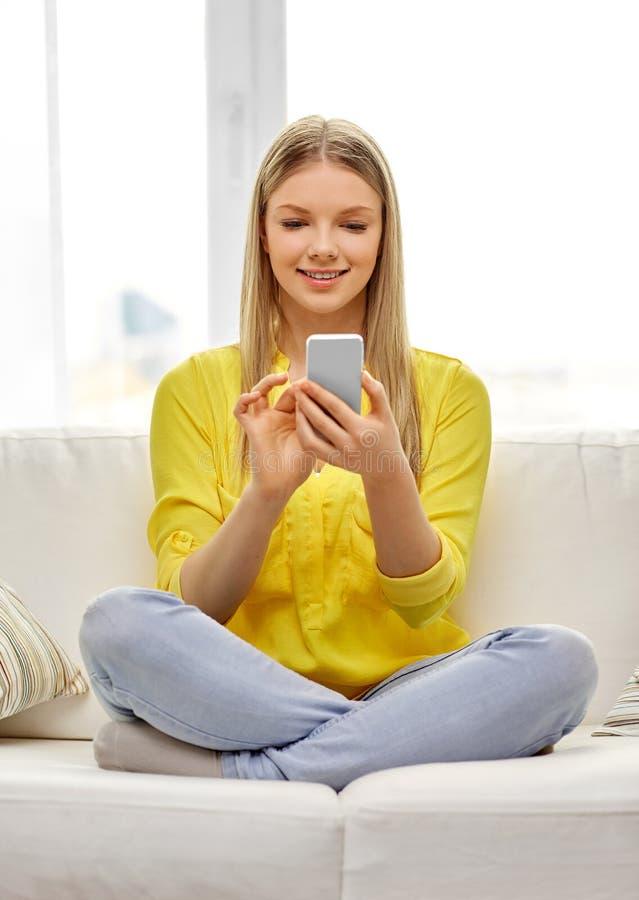 Ung kvinna eller tonårig flicka med smartphonen hemma fotografering för bildbyråer
