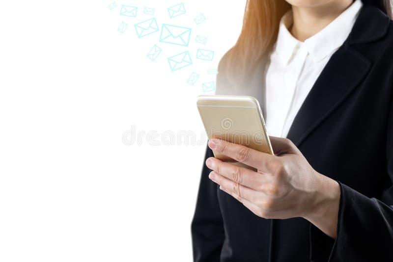 Ung kvinna för affär som bär svart dräktanseende genom att använda den mobila smarta telefonen som överför meddelandet eller över arkivbild