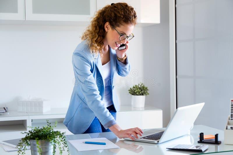 Ung kvinna för affär som talar på mobiltelefonen, medan genom att använda hennes bärbar dator i kontoret royaltyfri foto