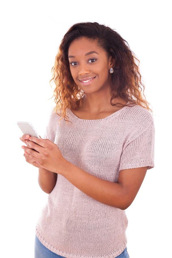 Ung kvinna för afrikansk amerikan som överför ett textmeddelande fotografering för bildbyråer