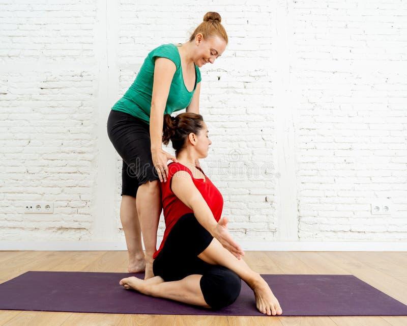 Ung kvinna för attraktiv för yogaterapeutlärare nybörjare för portion med yogaövning i studiohem royaltyfri bild
