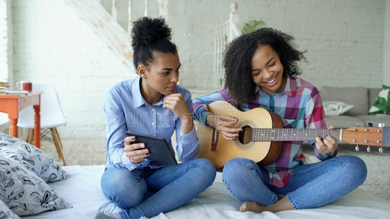 Ung kvinna för blandat lopp med minnestavladatorsammanträde på säng som undervisar hennes tonårs- syster att spela den akustiska  fotografering för bildbyråer