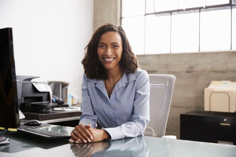 Ung kvinna för blandat lopp på kontorsskrivbordet som ler till kameran royaltyfri fotografi