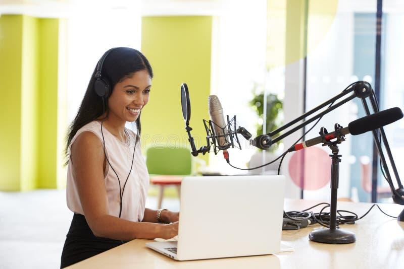 Ung kvinna för blandat lopp som antecknar en podcast i en studio arkivbild