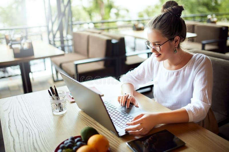 Ung kvinna för blandat lopp som arbetar med bärbara datorn i kafé på tropiskt läge Asiatisk caucasian kvinnlig som studerar genom royaltyfri foto