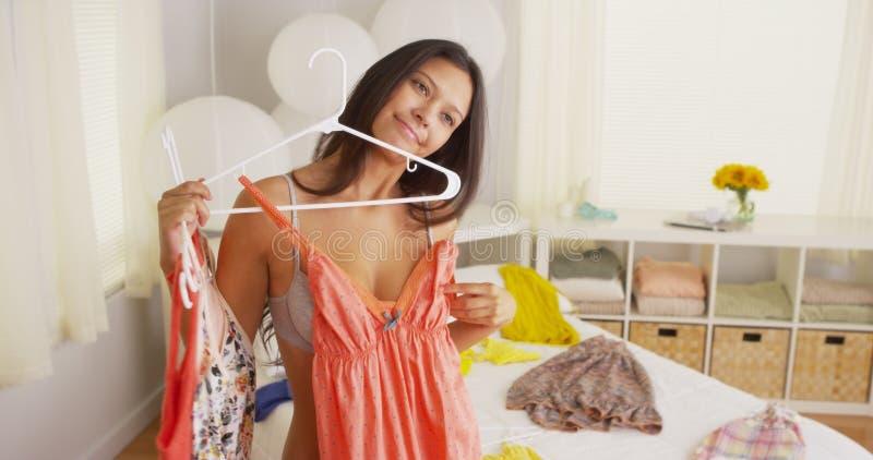 Ung kvinna för blandat lopp som försöker att figurera ut vad för att bära arkivfoton