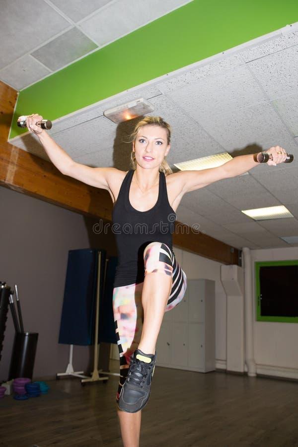 ung kvinna för blond skönhet i idrottshall som utarbetar med par av hantlar i hälso- och konditionbegrepp arkivbild