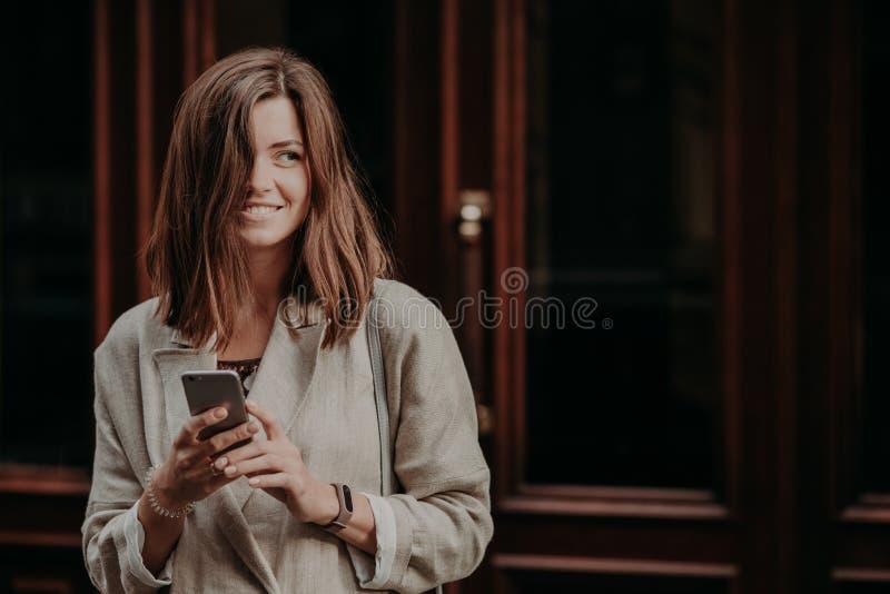 Ung kvinna för emotionell förtjust lycklig brunett med mörkt hår, bruksmobiltelefon för smsande meddelanden, iklädd elegant regnr arkivfoton