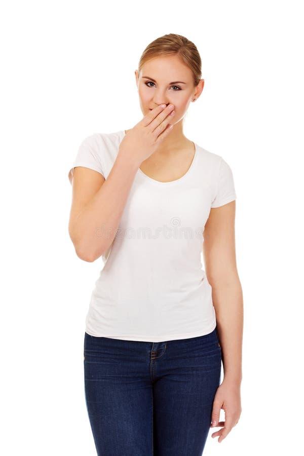 Ung kvinna för fniss som täcker hennes mun med handen royaltyfri foto