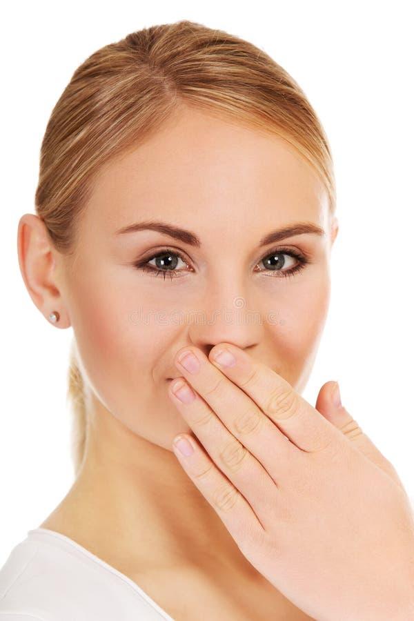 Ung kvinna för fniss som täcker hennes mun med handen royaltyfri fotografi