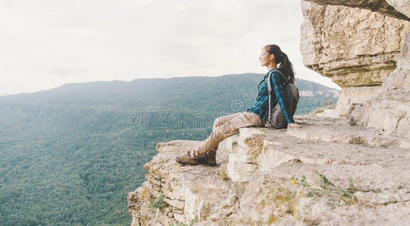 Ung kvinna för fotvandrare som vilar på klippan fotografering för bildbyråer