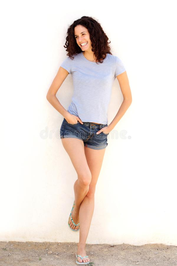 Ung kvinna för full kropp i kortslutningar som ler mot den vita väggen royaltyfri fotografi