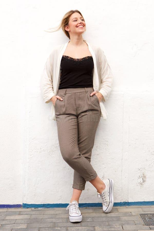 Ung kvinna för full längd som skrattar mot den vita väggen arkivbild