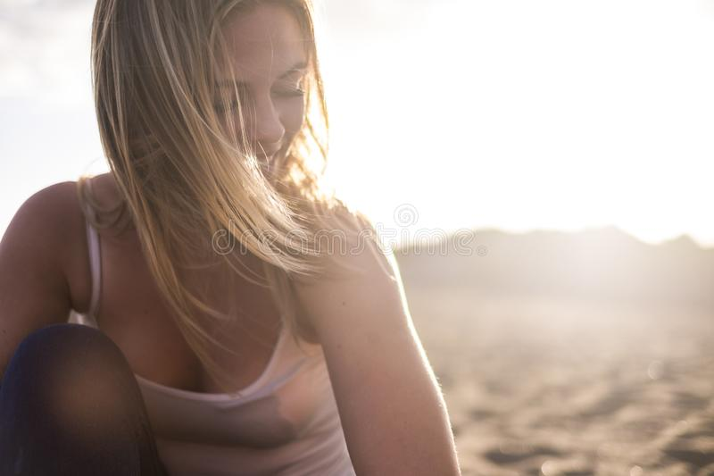 Ung kvinna för härlig blond modellflicka på stranden under solnedgången med solen i panelljus leende och att tycka om fritidsakti arkivfoton