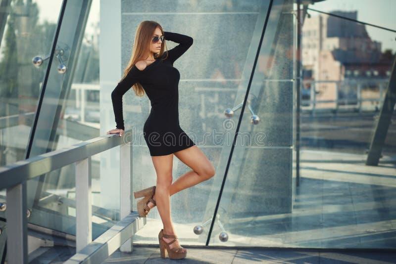 Ung kvinna för härlig brunett i den trevliga svarta klänningen, solglasögon, sandaler för höga häl bedsheetmode l?gger f?rf?riskt arkivfoto